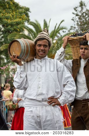FUNCHAL MADEIRA PORTUGAL - SEPTEMBER 4 2016: Man carry the barrel of wine in traditional costume durnig historical and ethnographic parade of Madeira Wine Festival in Funchal. Madeira Portugal