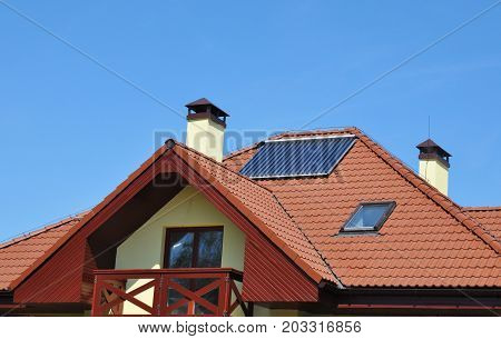 Energy efficiency concept. Closeup of solar water panel heating on red tiled house roof with lightning protection sky lights roof windowsgutter and chimney.