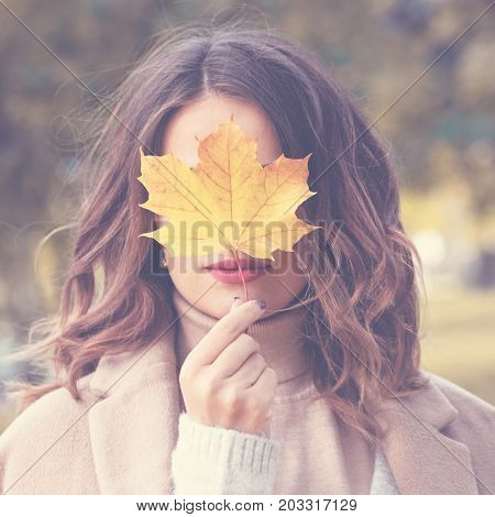 Beautiful Autumn Woman Holding Yellow Mapple Leaf Outdoors. Romantic Girl in Fall Park