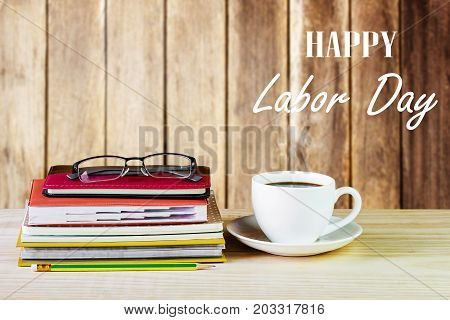 Labor Day is a federal holiday of United States America. Cup of Coffee glasses and stack of book on wooden table with blurred wood background. Business concept. Space for any design