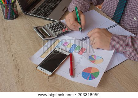 a business man working in home office table plan for business market analysis. Man hand with calculator at workplace offic. Home finances investment economy saving money or insurance concept