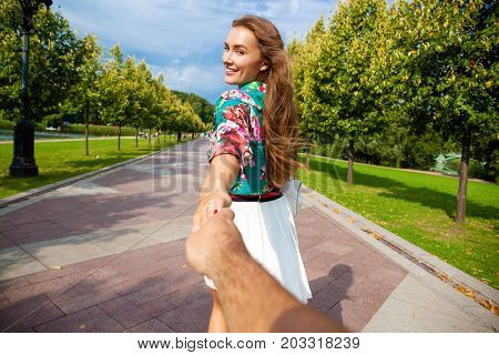 Follow me, Young beautiful woman pulls the arm of her boyfriend in a city park