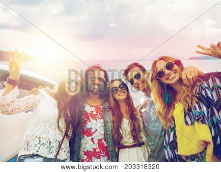 summer holidays, road trip, travel and people concept - smiling young hippie friends at minivan car showing peace hand sign over sea background