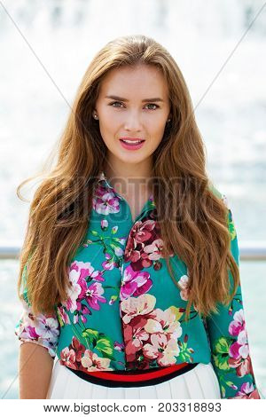 Young happy brunette woman in flowers blouse