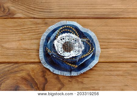 Blue denim floral brooch or hair accessory isolated on a wooden table. How to Recycle old jeans into a new jewelry. Beautiful handmade flower made from recycled materials. Cheap craft idea for adults