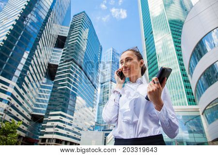 Beautiful young business woman calling by phone on the background of skyscrapers