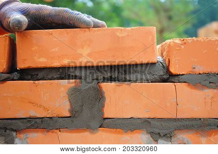 A closeup of a bricklayer worker installing red brick