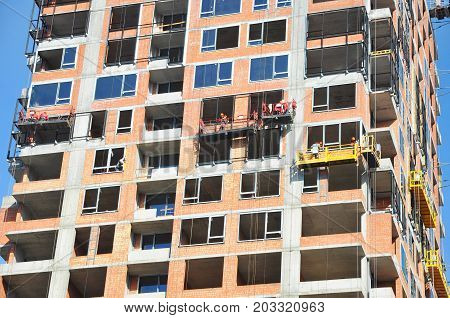 Surveying Large Building Site. Workers Building New House install Windows Wall Insullation Balkony. Industrial Building Construction.