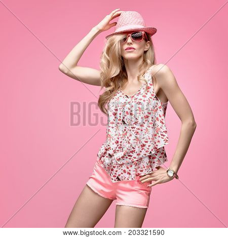 Fashion Hipster woman in Stylish Outfit. Cheeky emotion. Sexy Blond Model Crazy Girl, Fashion Sunglasses, Glamour Pink Shorts, Floral Top. Trendy pink fashion Hat. Summer Hairstyle