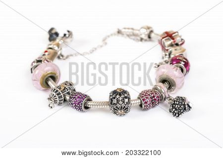 Silver charm bracelet with pink beads isolated on white background