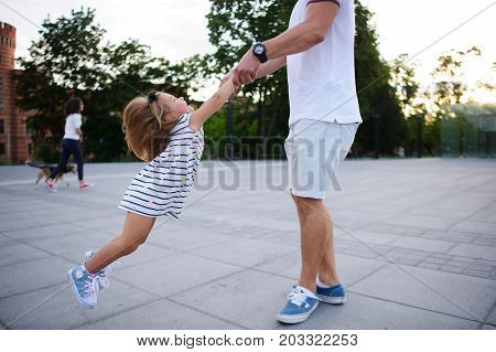 Young dad is playing with a charming little daughter. The man holds the baby by hands and is turned together with her. The child rejoices.