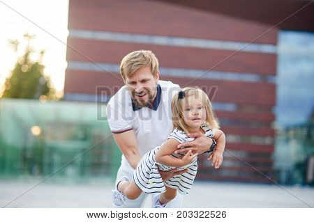 Young dad is playing with a charming little daughter. The man holds the baby on handsand is turned together with her. The child laughs with pleasure.