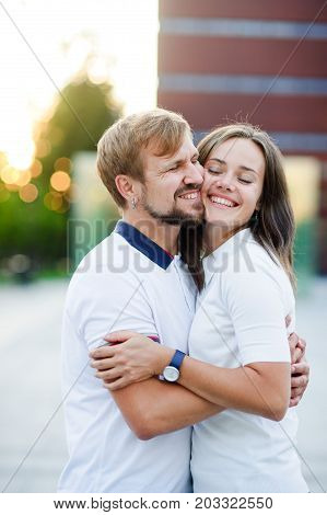 Portrait of beautiful young couple. Young people sit having nestled to each other cheek to cheek. They happily smile.