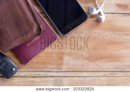 Smart phonewalletpassportand car key on wooden table with ear phone. Top view with copy space for design