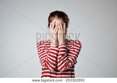 Pretty caucasian girl covers her face with her hands, feel embarrassed or shy.