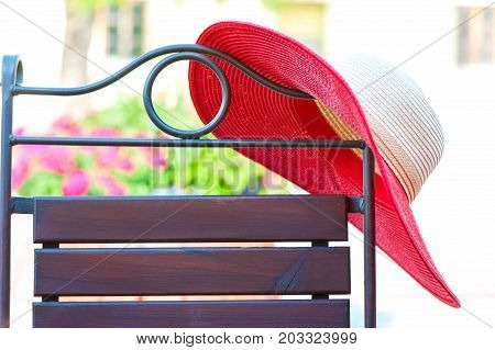 Part of elegant metal curved chair and red summer hat on patio. Outdoors.