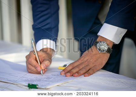 A closeup of a young man's hands in formal attire signing a legal document.