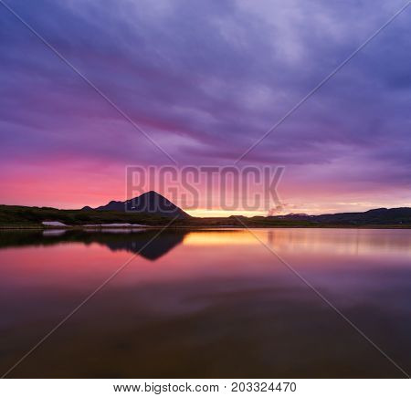 Polar day in Iceland. Colorful sunset on the lake. Amazing landscape with mountains