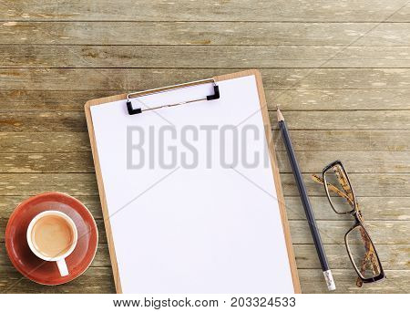 Office desk - Top view of brown wooden office table with cup of coffeeglassespencil and notepad. working office space. objects on the table. office working and business concept