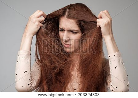 Pretty caucasian woman trying to comb hair. The problem with the tangled and long hair.