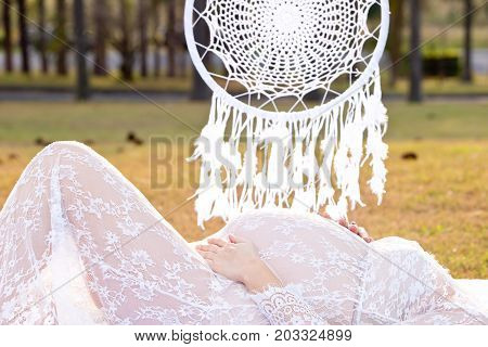 Pregnant Woman Laying Down In Field With Macrame Hanging Mandala In Background