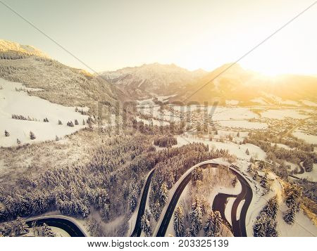 a mountain road is winding through a snowy landscape in the german alps