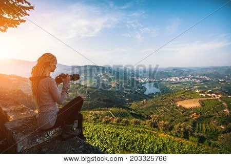 A young woman photographs the Douro Valley, Portugal. Top view of river, and the vineyards are on a hills.