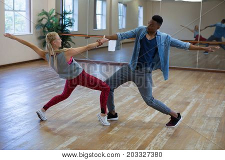 Full length of young dancers rehearsing against mirror on wooden floor at studio