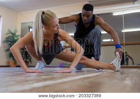 Dancer assisting female friend in stretching on wooden floor at studio