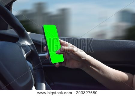 Asian men aged about 40 are using mobile phone while driving dangerous and illegal clipping path included to remove the background and phone green screen with ease