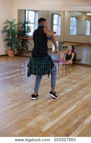 Male dancer rehearsing with friend sitting on hardwsood floor at studio