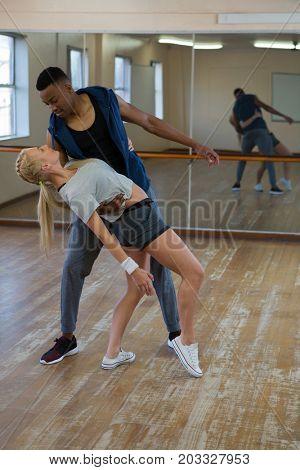 Full length of friends dancing on wooden floor at studio