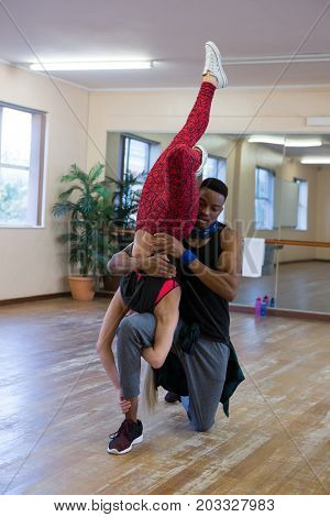 Young dancers rehearsing on wooden floor at studio