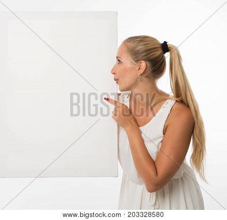 Young pry woman portrait of a confident businesswoman showing presentation, pointing placard gray background. Ideal for banners, registration forms, presentation, landings, presenting concept.