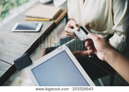 Waiter taking card from hands of the client to accept payment