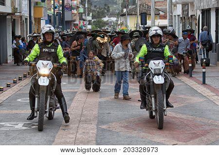 June 29 2017 Cotacachi Ecuador: motorized police leading indigenous quechua people at Inti Raymi summer solstice celebration