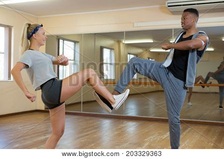 Friends practicing dance against mirror on wooden floor at studio