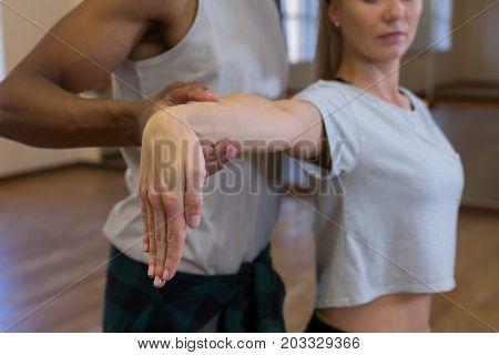 Man assisting female friend in dance on floor at studio