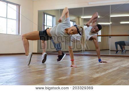 Full length of dancers practicing against mirror on wooden floor at studio