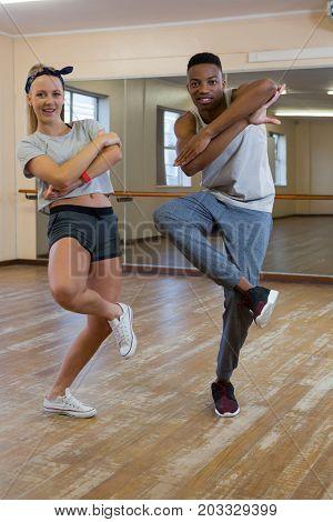 Full length portrait of friends rehearsing dance against mirror at studio