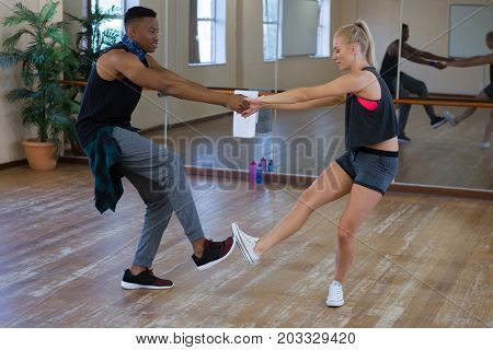 Side view full length of dancers practicing on wooden floor at studio