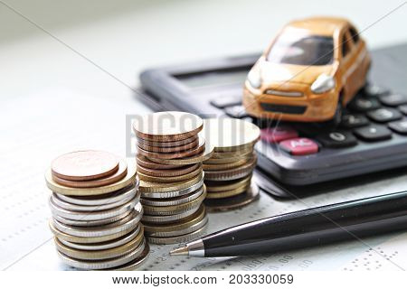 Business, finance, saving money or car loan concept : Miniature car model, coins stack, calculator and saving account book or financial statement on office desk table