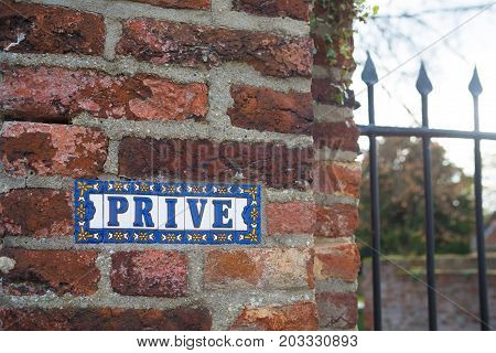 Prive (private in english) sign on a stone brick wall