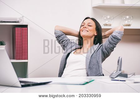Young businesswoman is daydreaming in her office.