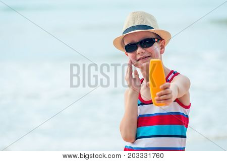 A 7 Year Old Boy Shows A Protective Sun Cream And Smears His Skin On The Beach