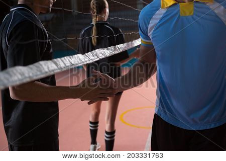 Male volleyball players shaking hands through net at court