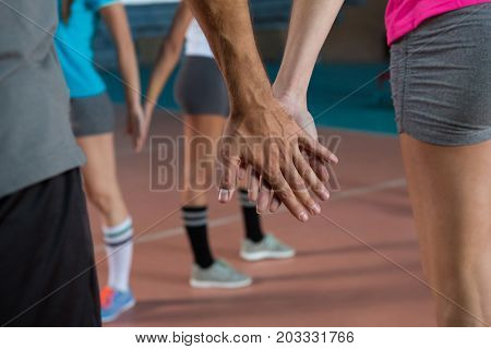 Mid section of volleyball players holding hands at court