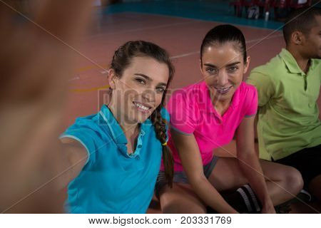 Portrait of smiling volleyball players relaxing at court