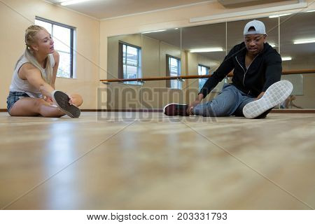 Full length of dancers stretching on wooden floor at studio