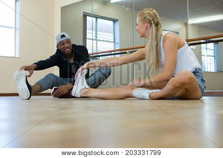 Full length of young dancers stretching on wooden floor at studio